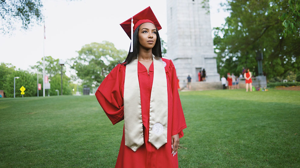 Ruhama Wolle stands in her red cap and gown in front of the NC State belltower